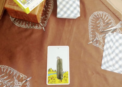 Rider-Waite five of cups in the bottom of the photo resting on a brown cloth with printed scissors on it. Other cards are face down in piles with blue plaid-ish designs. A small wooden box is barely in frame at the top of of the image and on the RIder-Waite box is resting.