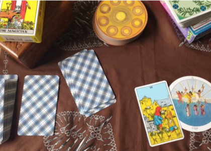 Spread of cards on a brown cloth with a printed design of scissors. Three decks are visible face down, the Rider-Waite, The Herbal Tarot and the Motherpeace which is circular and golden with a design of circles. A wooden box is in the upper left hand corner. In the bottom right/center there is the Rider-Waite six of cups and the Motherpeace six of cups.