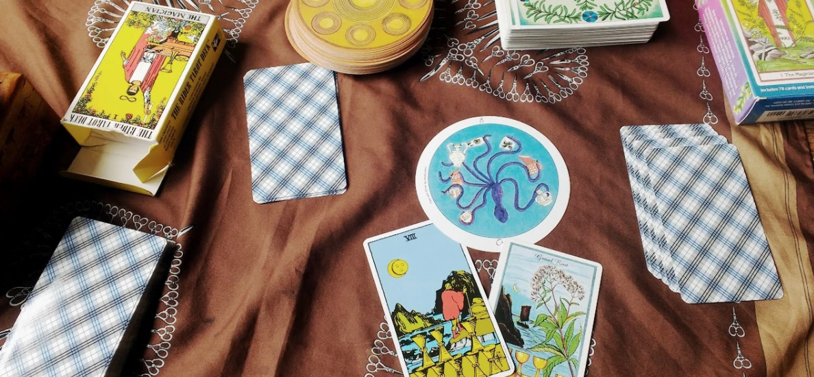 """A brown cloth with scissor designs printed on holds a scene of tarot cards. Three stacks of face-down Rider-Waite cards are scattered around, the Motherpeace tarot is in one pile and the Herbal tarot is in another. The Rider-Waite and Herbal Tarot boxes are visible on the upper left and right sides of the image respectively. In the lower middle are three cards, each of them the Eight of Cups from the three decks in the photo. The Motherpeace tarot features a purple octopus in a blue ocean holding a shell in each tentacle. The Rider-Waite shows a person in a red tunic with yellow tights and red boots holding a walking stick traversing what appears to be a rocky beach shore. In the background are some large rocks coming out of the ocean. There appears to be a partial eclipse in the background. In the foreground are eight stacked cups. The herbal tarot shows an ocean shore scene with a sailboat in the background, eight cups stacked in the foreground, and a picture of flowering fennel. The top says """"fennel root""""."""