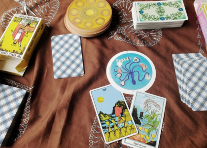 "A brown cloth with scissor designs printed on holds a scene of tarot cards. Three stacks of face-down Rider-Waite cards are scattered around, the Motherpeace tarot is in one pile and the Herbal tarot is in another. The Rider-Waite and Herbal Tarot boxes are visible on the upper left and right sides of the image respectively. In the lower middle are three cards, each of them the Eight of Cups from the three decks in the photo. The Motherpeace tarot features a purple octopus in a blue ocean holding a shell in each tentacle. The Rider-Waite shows a person in a red tunic with yellow tights and red boots holding a walking stick traversing what appears to be a rocky beach shore. In the background are some large rocks coming out of the ocean. There appears to be a partial eclipse in the background. In the foreground are eight stacked cups. The herbal tarot shows an ocean shore scene with a sailboat in the background, eight cups stacked in the foreground, and a picture of flowering fennel. The top says ""fennel root""."