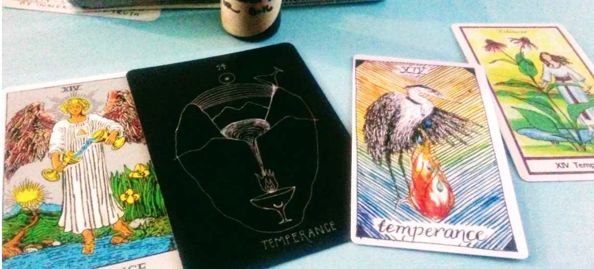 Four temperance cards from left to right: Rider-Waite, Wanderer's Tarot, Wild Unknown, Herbal Tarot. Rider-Waite shows a humanlike angel figure wearing a white robe with a gold, upward pointing triangle on it. The angel has red wings and a halo of light around their head. They have what appears to be white skin and blonde hair. They pour water from one cup into another. The scene they stand in is at a pond at the end of dirt path, the sun rises above mountains in the distance. There are yellow lilies to their left. Wanderer's Tarot shows a chalice pouring water into a mountain valley, from there the water pools and is pouring into a chalice with a crescent moon symbol on it filled with fire. There appears to be a rainbow and sun above the mountain scene. The wild unknown has rainbow small chevron pattern background with a Heron shedding tears into a flame. The Herbal Tarot shows a European looking, white skinned figure with brown hair wearing white robes with a purple red sash at a pond. In the forground is an Echinacea plant with purple flowers in bloom.