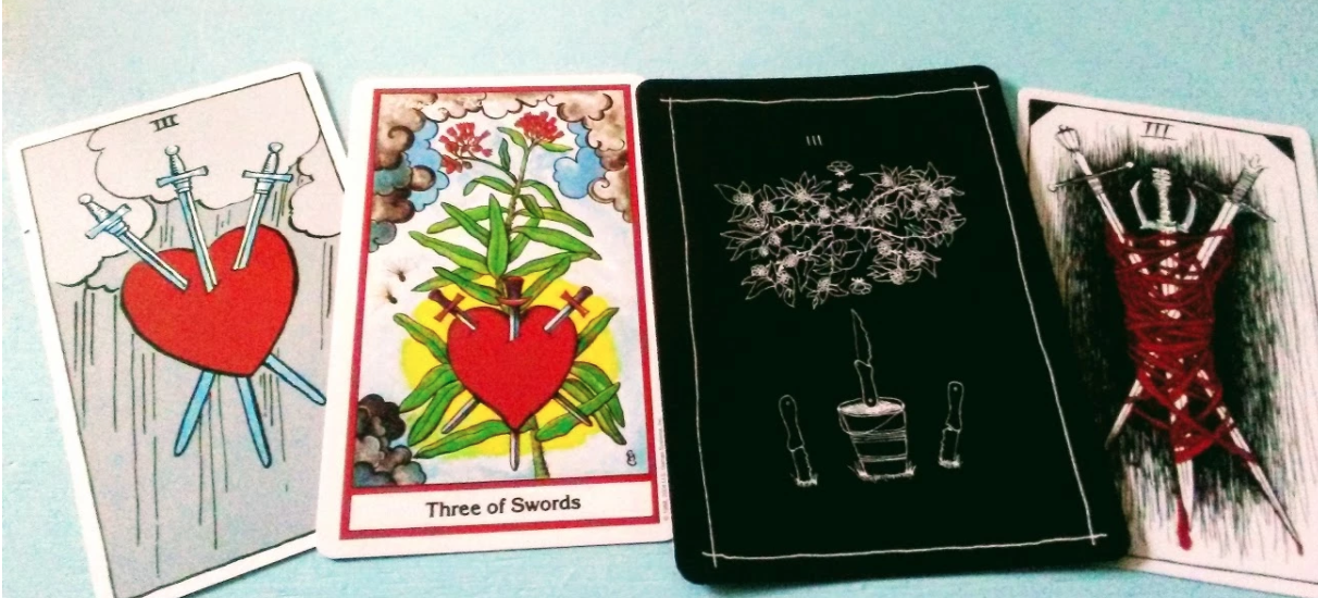 Four versions of the three of swords from four decks. Left to right: RIder-Waite, Herbal Tarot, Wanderer's Tarot, and Wild Unknown. Rider-Waite is a red heart with three swords in it on a background gray rainy scene. Herbal tarot is also a red heart with three swords with a bright sun shining behind it and a pleurisy plant with red blossoms. The Wanderer's tarot shows a tangled thorny bush hovering over a bucket on which a knife floats pointing upwards on water. Two knives stuck in the ground flank the bucket. The Wild Unknown pictures three swords tangled in red string, each blade appears to be dripping blood.