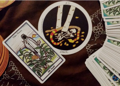 A brown cloth with scissor designs printed on holds two Death tarot cards, one from the Herbal Tarot and the other from the Motherpeace tarot. The cards are surrounded by the turned-down decks fanned out. The Herbal Tarot shows elder flowers in the foreground. Behind the elder is a figure in a white cloak with a face obscured in shadow. Behind the figure is a mountain sunset landscape scene. The Motherpeace tarot shows a skeleton in the fetal position at the base of an alder tree surrounded by scattered yellow leaves. A red and yellow snake circles around the skeleton shedding its skin.