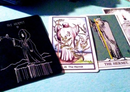 Four versions of The Hermit tarot card. Left to right: Wanderers, Herbal Tarot, Rider-Waite, and Wild Unknown. The Wanderers shows a faceless cloaked figure with a candle for a face standing on a cliff, their arm is outstretched palm facing outward as they shine a light from their hand. Herbal Tarot is a hooded figure back turned to the viewer holding a crystal ball to the sky in one hand and holding a walking stick in the other. A licorice plant stands in the foreground. Rider-Waite shows a gray cloaked bearded figure holding a yellow walking stick in one hand and holding up a lantern in the other. Wild Unknown shows a turtle tucked into it's shell with a lit candle on their back.