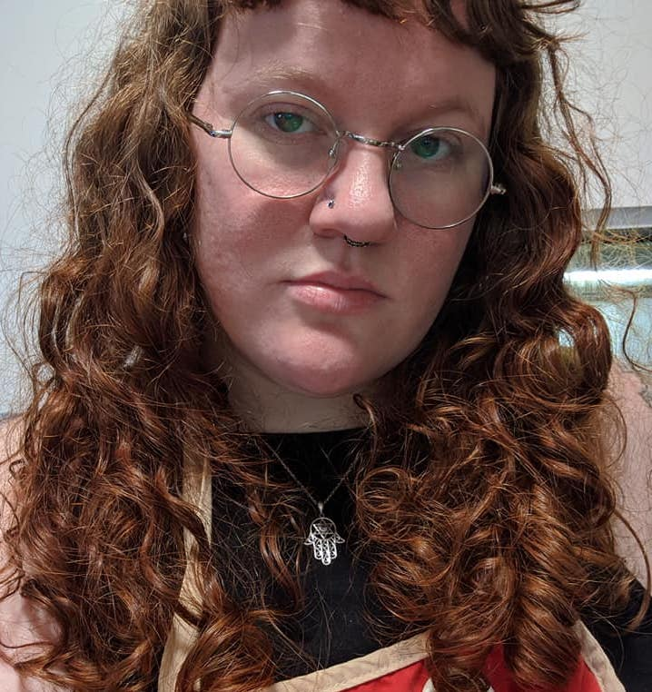 A photo of Juniper- a white nonbinary person with round silver glasses, green eyes and long, red curly hair. They are wearing a hamsa necklace and a black shirt.