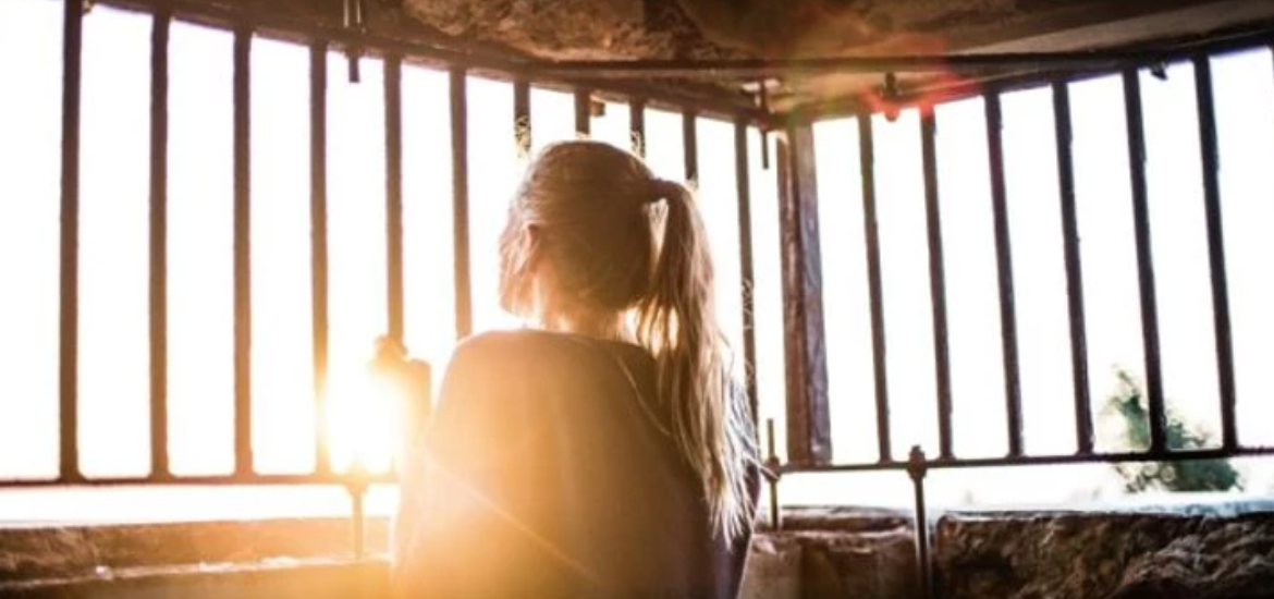 Photo of a blonde white person with a ponytail, back to the camera looking longingly through bars at a sunset.