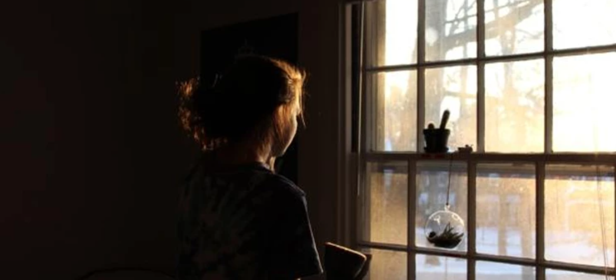 A person in a tie dye shirt with a ponytail in a dimly lit room looks out a window. There is snow on the ground outside and golden sunlight comes in through the window, gently lighting their face and hair.