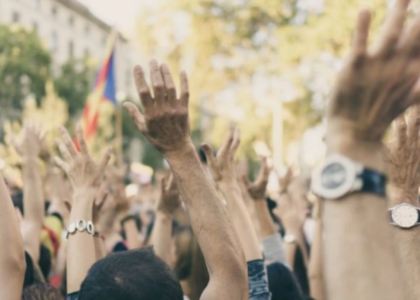 Many hands are raised in the air at a daytime demonstration. Only hands and tops of heads are visible.